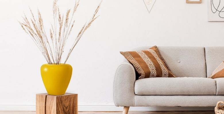Yellow FRP Planter on a wooden box near sofa in a living room